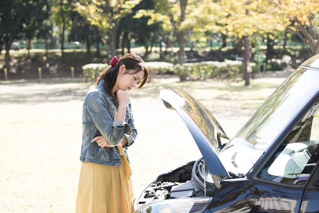 車のボンネットをあける女性